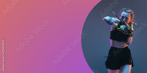 Tela Young female MMA fighter posing isolated over pink gray background in neon light