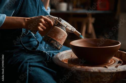 Obraz na plátne Image of process modeling ceramic bowl with special instrument in pottery worksh