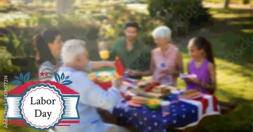 Composition of labor day text and logo over family having celebration picnic