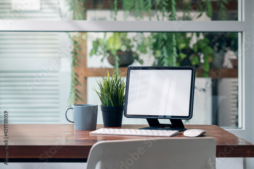 Fotografie, Obraz Mockup blank screen tablet on stand with keyboard on wooden table in living room