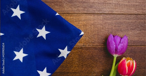 American flag and red and purple tulip flowers on wooden background
