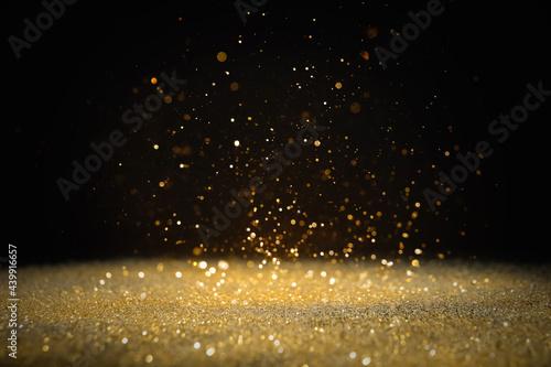 Billede på lærred Shiny golden glitter falling down on black background