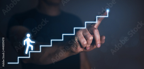 Businessman pointing to the growing plan of successful business and a figure climbs the ladder of success. Start-up concept.