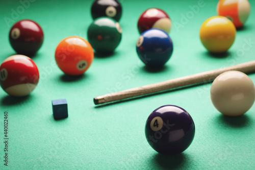 Obraz na plátně Many colorful billiard balls, cue and chalk on green table