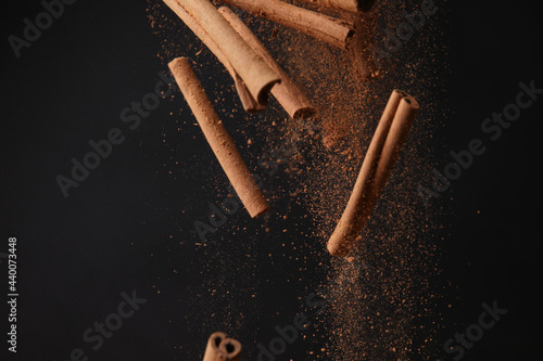 Photographie Falling cinnamon sticks and powder on dark background