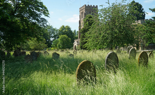 Fotografiet Eaton Socon Church and churchyard with grass left uncut in graveyard to encourage insects