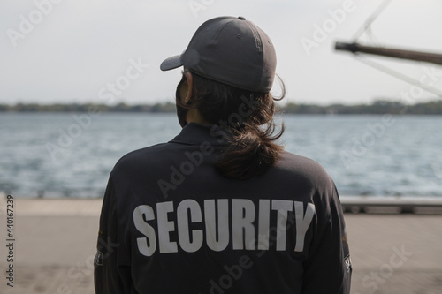 Photo Closeup shot of a female security guard in uniform and mask watching over the ha