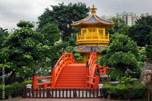 Obraz na plátně Chinese pagoda and red bridge in a park among skyscrapers in a big city