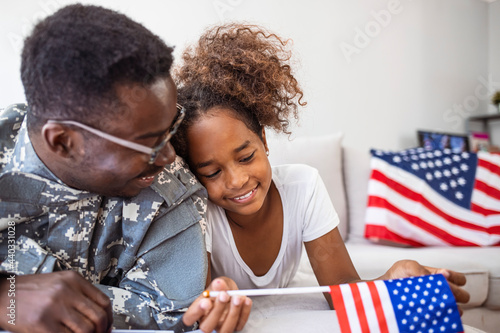 Fototapeta Portrait of happy american family father in military uniform and cute little gir