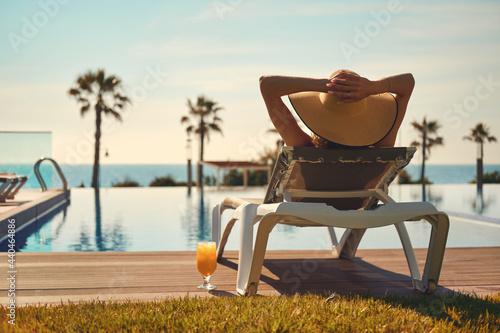 Canvas Print Rear view woman wear hat sunbathing on deckchair on poolside