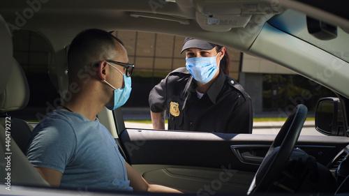 Obraz na plátně Police officer checking male driver during pandemic