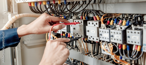 Canvastavla Electrician engineer uses a multimeter to test the electrical installation and power line current in an electrical system control cabinet