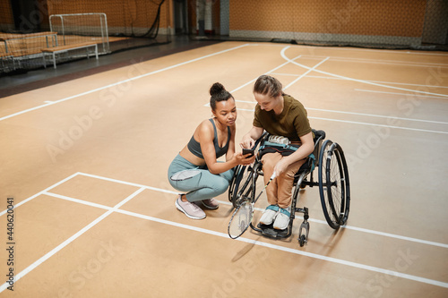 Billede på lærred High angle view at young woman in wheelchair talking to female coach during badm