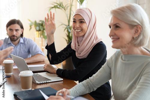 Obraz na plátně Smiling Asian muslim businesswoman wearing hijab raising hand close up, asking q