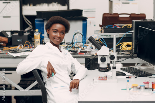 Canvastavla Scientist african american woman engineer working in laboratory with electronic tech instruments and microscope