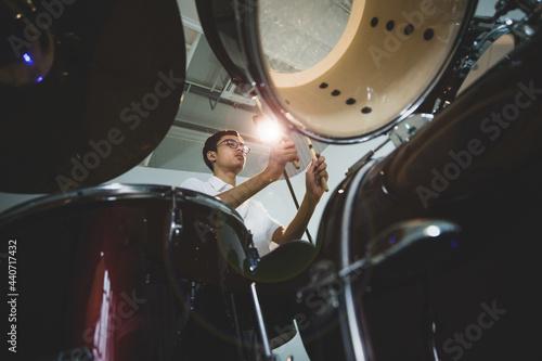 Billede på lærred Ant-eye view portrait shot of a teenage drummer playing the drum on the stage