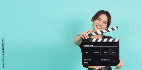 Fotografering Woman holding black clapperboard or movie slate use in video production ,film, cinema industry on green mint or Tiffany Blue  background