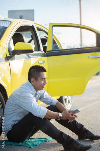Latino man sitting next to a yellow vehicle while checking the cell phone Fotobehang