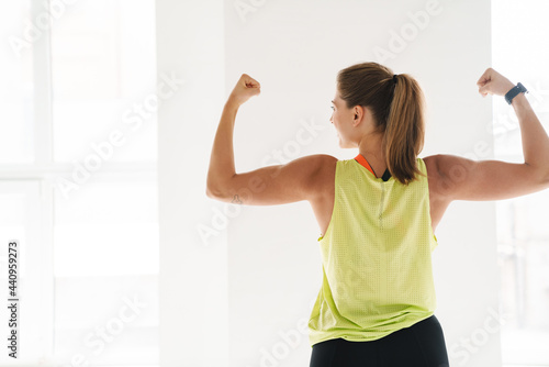 Canvas Smiling fitness woman show her biceps at gym