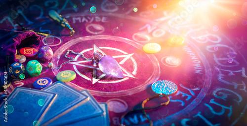 Fotografia Cartomancy And Tarot - Pendulum On Altar With Defocused Cards And Chakra Stones