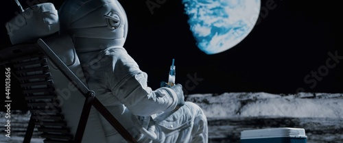 Fotografija Back view of lunar astronaut opens a beer bottle while resting in a beach chair