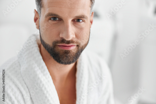 Fototapeta Positive man with styish waits for beauty procedures in cosmetologycal clinic