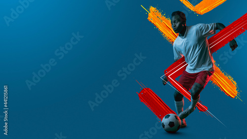 Canvas Print Young man, soccer footbal player training isolated in neon light background