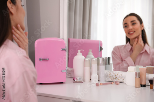 Obraz na plátně Woman getting ready at dressing table with cosmetic fridge indoors