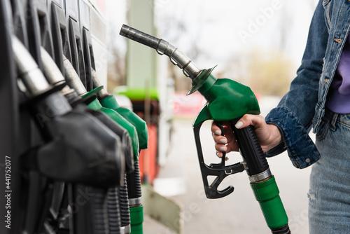 Obraz na plátně cropped view of woman holding petrol pistol on gas station