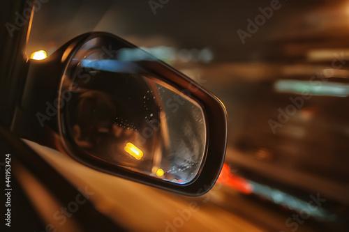 Carta da parati night trip on car background, abstract blurred rear view mirror urban road