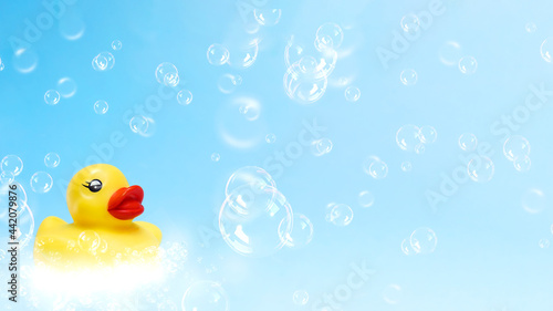 Stampa su Tela Yellow rubber duck on light blue background with soap bubbles.
