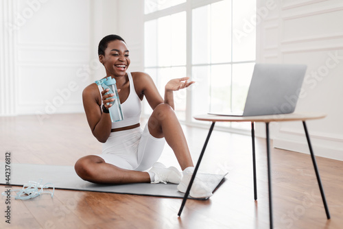 Young black woman woman exercising with online trainer using pc Fototapeta