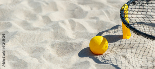 Obraz na plátne Spike ball game with yellow ball on sand. Summer game concept