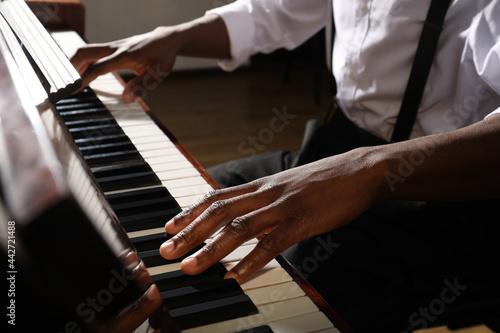 Obraz na plátně African-American man playing piano indoors, closeup