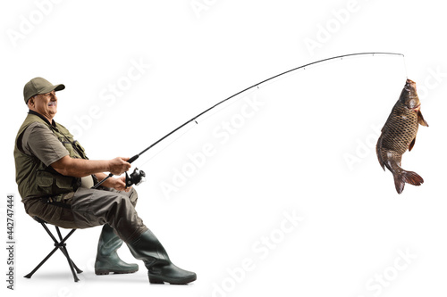 Fotografie, Obraz Fisherman sititng on a chair and catching a big carp fish