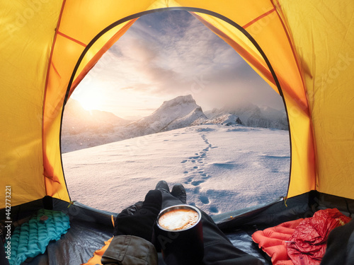 Man holding coffee cup and enjoying view of sunrise on snowy mountain inside yel Fototapet