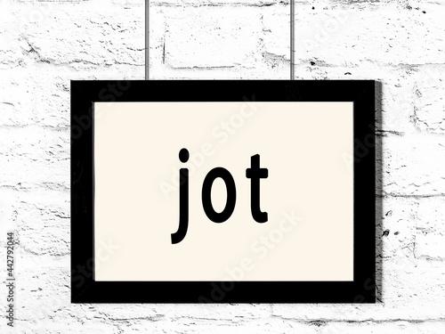 Black frame hanging on white brick wall with inscription jot Fototapet