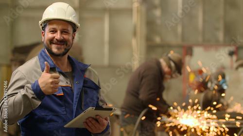 Fotografie, Obraz Engineer looking at camera smiling and showing thumb up at metallurgy plant