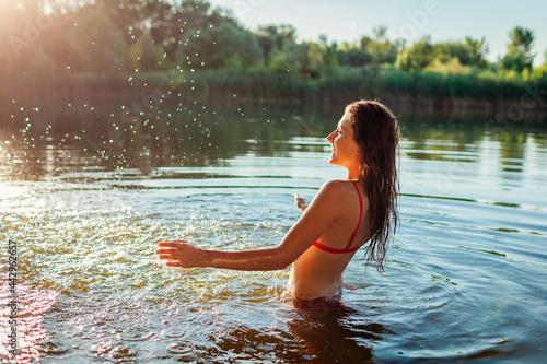 Canvas Young happy woman in bikini having fun in water and making splash