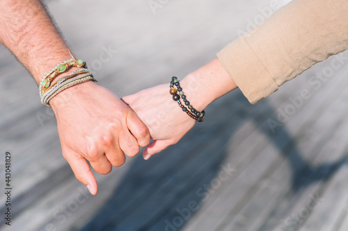 Tablou Canvas Male and female hands with boho chic bracelets holding each other, fashion photo