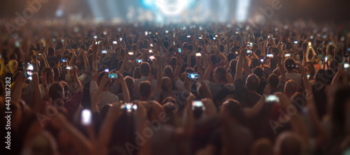 Fotografering people at a concert are filming on a smartphone.