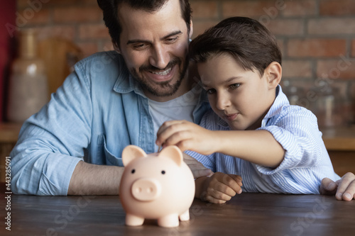 Canvas Print Happy dad teaching smart little son to save and invest money, encourage kid for accounting, investment, planning future budget