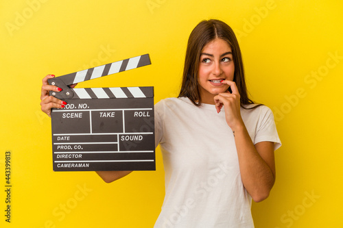 Canvastavla Young caucasian woman holding clapperboard isolated on white background relaxed thinking about something looking at a copy space