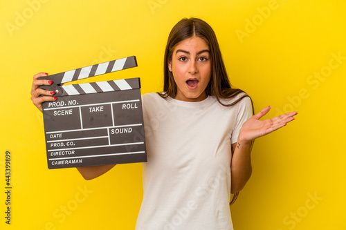 Young caucasian woman holding clapperboard isolated on white background surprised and shocked Fototapeta