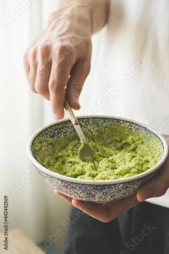 Fotografija Male chef mashing avocado with fork in a bowl