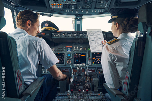 Fotografering Pilot and female first officer seated in the flight deck
