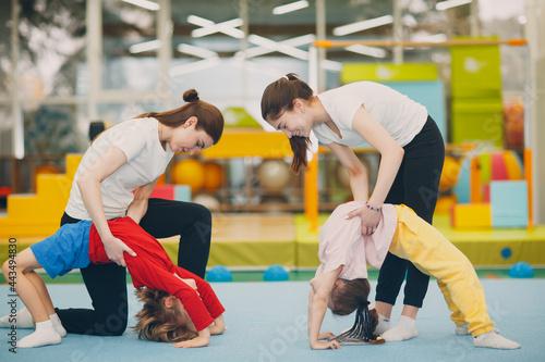 Foto Kids doing exercise bridge in gym at kindergarten or elementary school