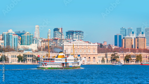 Fotografering Sea voyage with old ferry or steamboat in the Bosporus - Dolmabahce Palace  seen