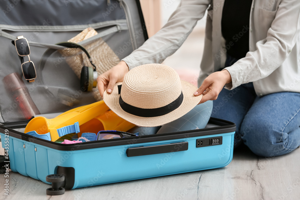 Obraz Woman packing suitcase at home fototapeta, plakat