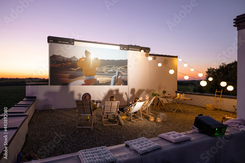 Small group of people watching movie on the rooftop terrace at sunset Fotobehang